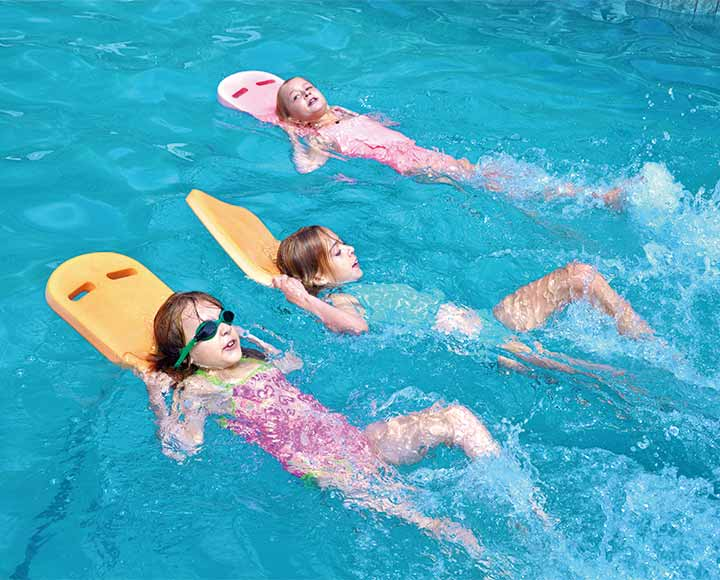Children using swimming kickboard in pool